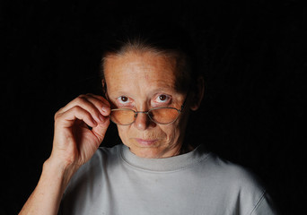 Middle aged woman with glasses with dark background