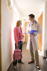 Doctor and girl with backpack talking in corridor