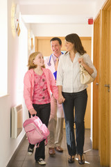 Mother and daughter holding hands in corridor with doctor in background