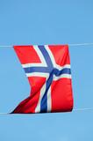 Small Norwegian flag against blue sky poster