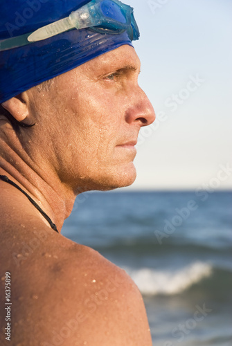 mature male swimmer wearing cap and goggles.