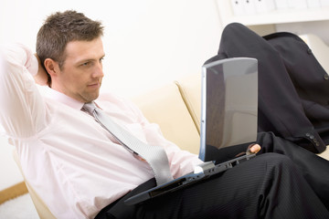 Relaxed businessman using laptop