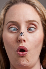 Woman surprised by fly on her nose