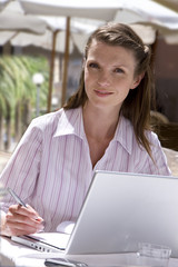 Smiling businesswoman working on laptop at outdoor cafe