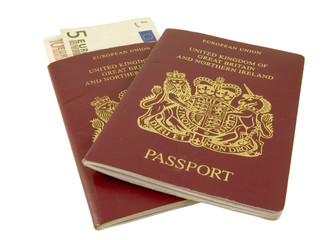 two british passports with euros isolated on white