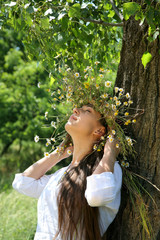 young gerl in the forest with diadem with wild flowers