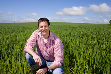Smiling farmer in field of young wheat