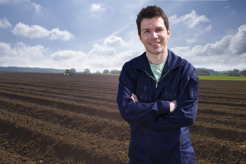 Smiling farmer standing in ploughed field