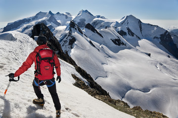 Mountaineer walks down along a snowy ridge