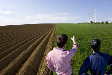 Farmers standing in young wheat field next to ploughed field and pointing at wind turbine in distance