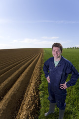 Smiling farmer standing with hands on hips in young wheat field next to ploughed field