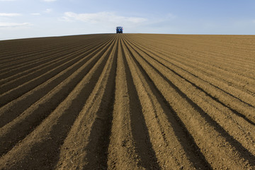 Ploughed field with tractor in distance