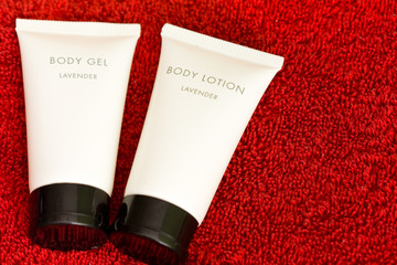 Lavender body gel and lotion, with no brand on a red towel
