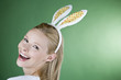 A young blonde woman wearing rabbit ears, laughing