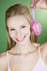 A portrait of a young blonde woman holding a pink Easter egg