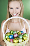 A young woman holding a basket full of Easter eggs, smiling