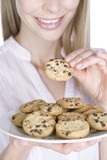 A young blonde woman holding a plate of cookies, smiling