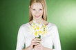 A young blonde woman holding a bunch of daffodils, smiling