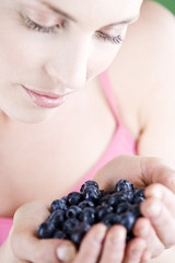 A young woman holding a handful of blueberries