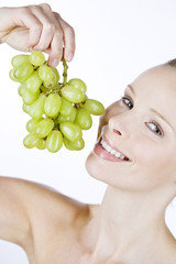 A young woman holding a bunch of grapes