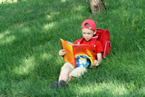 The boy reads the textbook sitting on a grass poster