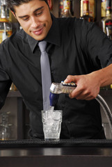 Bartender pouring soda on a drink.