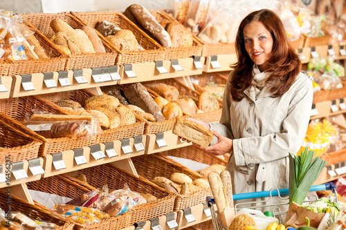 Grocery store: Young woman choosing bread