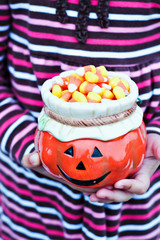 Child's hands holding a candy dish of Halloween candy.