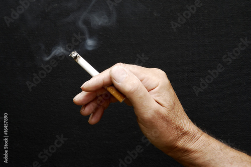 Male hand holding smoking cigarette