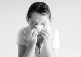 Young girl blowing nose