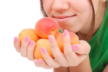 The female hands holds apricots near face