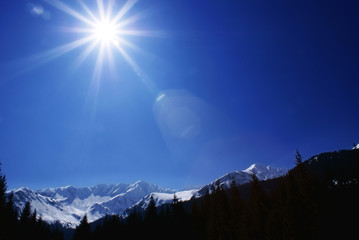 Sun and blue sky above winter landscape