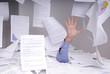 homme d'affaires se noyant dans un bureau pleins de papiers
