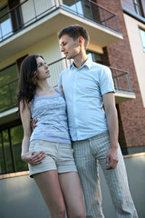 Couple in front of house in modern residential area.