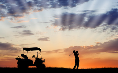 Silhouette of golfer with golf cart
