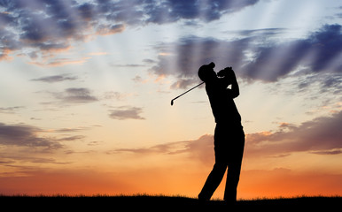 Golfer silhouetted against beautiful sunrise