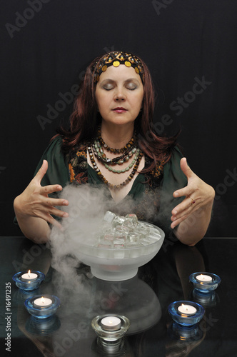 Lady with eyes closed practicing witchcraft on black
