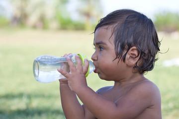 bambino  che beve acqua dal  biberon