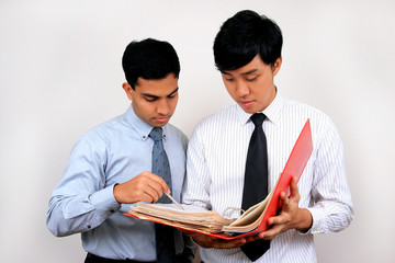 Indian and Chinese businessman looking at a file.