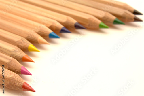 coloured wooden crayons lie next to each othe