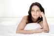 Beautiful woman lying on bed hesitating isolated on white