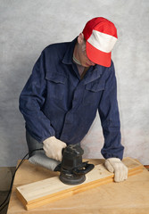 The worker polishes wooden board