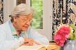 Seniorin liest ein Buch am Schreibtisch III