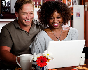 Mixed race couple in coffee house with laptop computer