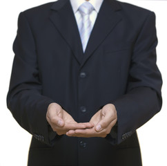 man clothed in suit holds his hands together