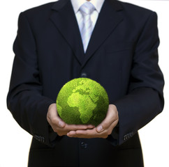 Businessman holding green planet