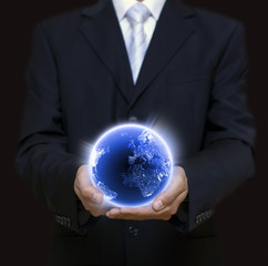 Businessman holding blue planet in the night full of lights