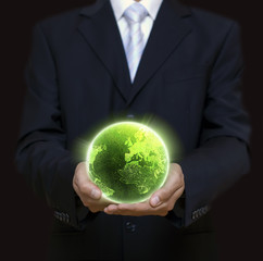 Businessman holding green planet in the night full of lights