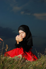 Little muslim girl on meadow, before sunset