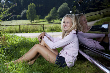 junge Frau lehnt an Auto